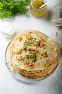 Traditional Russian pancakes with salmon and herbs