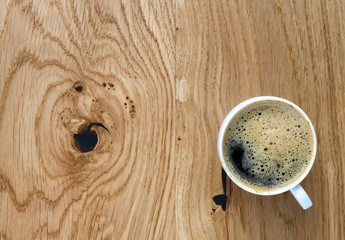 Top view of a cup with coffee on a wooden table.