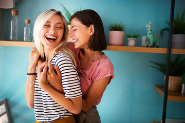 Cheerful lesbians embrace passioantely and have fun together