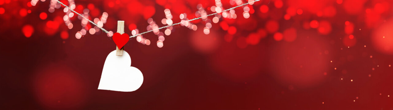 Happy Valentine's Day background banner panorama - White heart hang on wooden clothes pegs with wooden heart and bokeh lights on a string isolated on red texture, with space for text