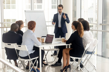 Male coach make whiteboard presentation for diverse employees