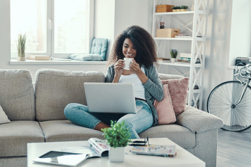 Attractive young African woman in casual clothing drinking hot tea and using laptop while resting at home
