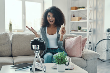 Happy young African woman holding beauty product and smiling while making social media video