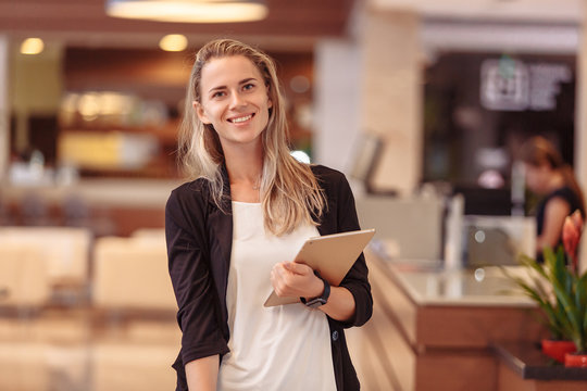 Beautiful young smiling caucasian woman hotel manager posing in the lobby. Woman IT developer with tablet stands in the lobby of her large company. Successful beautiful woman concept