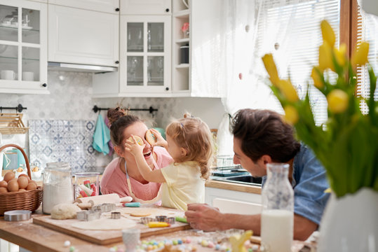 Playful family enjoy baking cookies together