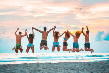 Happy successful friends jumping on the beach