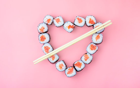 Salmon sushi rolls laid out in the shape of a heart on a pink background. The concept of Japanese cuisine for Valentine's Day, greeting card, banner. Copy space