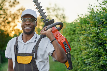 Portrait of smiling afro man in overall with hedge trimmer