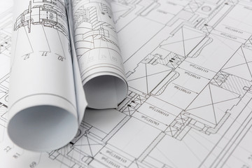 Technical drawings with blueprints in rolls close up. Engineering concept