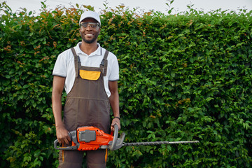 Front view of afro gardener with gasoline hedge trimmer