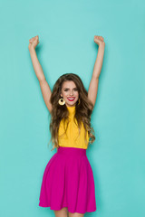 Confident Woman In Vibrant Clothes Is Holding Arms Raised