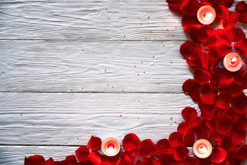 Red rose petals and red burning candles on a white wooden background. St. Valentine's Day background.