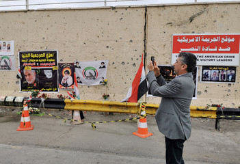 A man takes pictures at the site of U.S drone attack that killed the Iranian Major-General Qassem Soleimani, head of the elite Quds Force of the Revolutionary Guards, and the Iraqi militia commander Abu Mahdi al-Muhandis at the main road of Baghdad interna