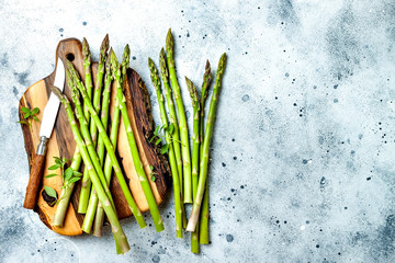 Wall Murals Lily of the valley Bunch of fresh green asparagus on wooden board with seasonings. Top view, copy space