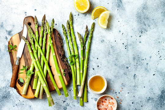 Bunch of fresh green asparagus on wooden board with olive oil, lemon and seasonings. Top view, copy space