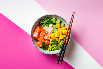 Hawaiian salmon poke bowl with seaweed, avocado, edamame, mango and pickled ginger. Top view, bright pink background