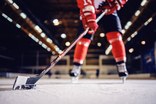 Close up of hockey player skating with stick and puck.