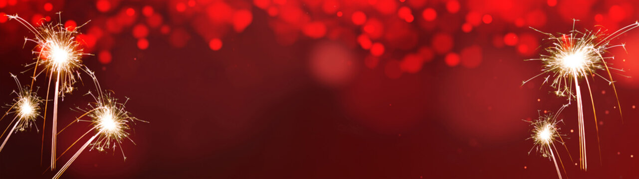 Silvester festive background panorama banner long - Sparklers on red texture with bokeh lights and space for text