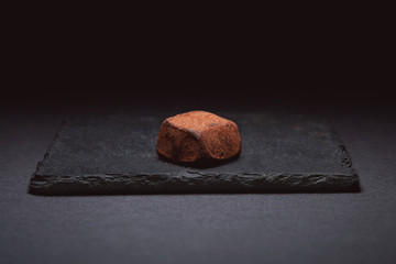 Truffle  sprinkled with cocoa.  Dark chocolate handmade truffle candy on a dark brown background