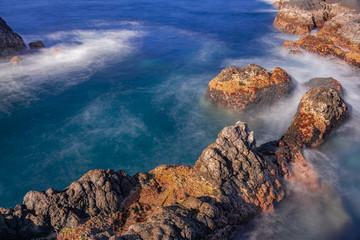 Volcanic rocks in Atlantic ocean, long exposure photography, with afternoon sunlight, Garachico, Tenerife, Canary islands, Spain