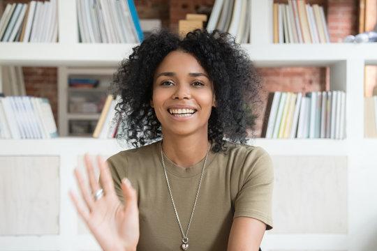 Smiling black woman waving talking on webcam