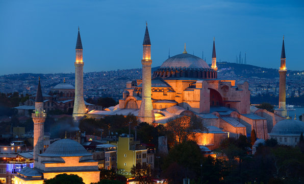 Lights on Hagia Sophia and Firuz Aga Mosque at dusk in Istanbul Turkey