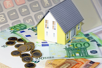 Model house with (euro)banknotes and coins as a concept photo for high real estate prices