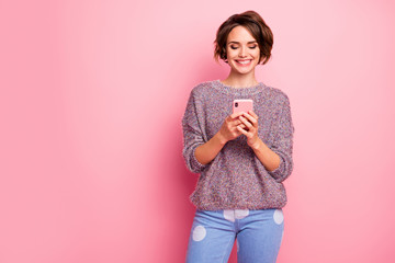 Portrait of her she nice attractive lovely charming pretty cute focused cheerful cheery brown-haired girl using cell sending sms web service isolated over pink pastel color background Wall mural