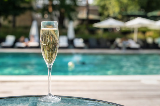 Close-up white champagne or prosecco glass against poolside at luxury resort hotel during vacation. Sparkling wine with rising bubbles with blue pool background outdoor. Refreshing alcohol drink