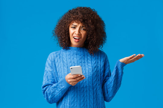 Wtf going on, someone explain me. Confused and frustrated bothered african-american woman in winter sweater, shrugging raise hand in dismay look questioned and pissed, holding smartphone
