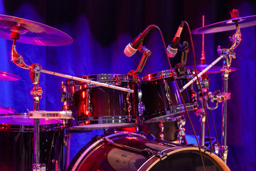 Drum set with bass drum, tom-toms, cymbals and microphones on the stage with blue-red illumination