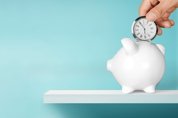 Hand depositing  clock  in piggy bank on background