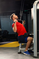 Young muscular man pulling up on horizontal bar in a gym