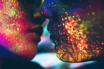 Couple kissing in the disco club with fluorescent paintings on the faces