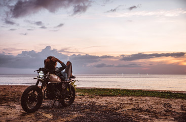 Beautiful girl having fun driving her custom cafe racer motorcycle, enjoying the sunset on the beach Fototapete