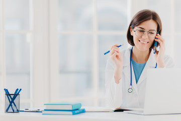 Photo of glad woman therapist or physician has phone conversation with patient, gives advice how to cure disease, wears white gown, reads information on laptop computer, works in private clinic