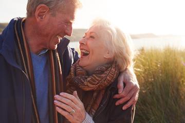Loving Active Senior Couple Hugging As They Walk Through Sand Dunes