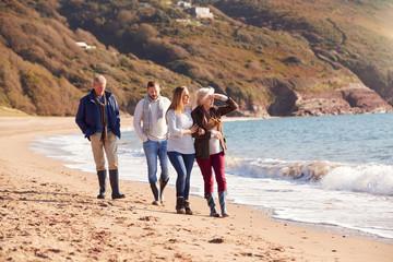 Foto op Canvas Marokko Senior Couple Walking Along Shoreline With Adult Offspring On Winter Beach Vacation