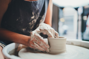 Obraz It's all about form! Closeup Image of Female Ceramic Artist Working With Pottery Wheel Makes Shape of Future Mug, Process in Pottery Workshop Creative People Handmade Products - fototapety do salonu