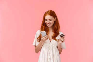 Shopping, easy payment and people concept. Lovely redhead girl in white dress picking present in...