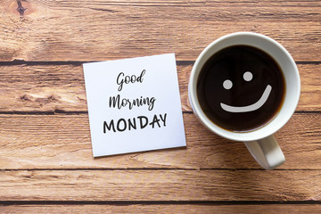 Good Morning Monday greeting on paper note with cup of coffee