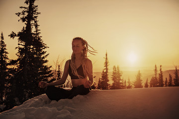 Young female wearing long hair dreads, seating in yoga lotus pose and meditating on sunrise in snow forest on mountain top. Cold frozen winter morning