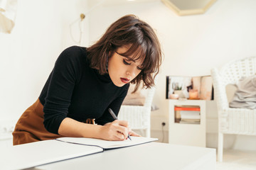 Young fashion designer using sewing machine