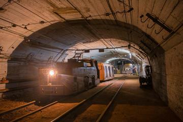 Underground gold bauxite mine shaft tunnel with electric locomotive
