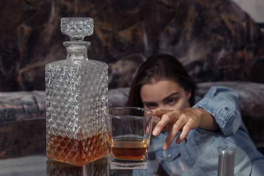 Office worker has alcohol addiction. Depressed young lady drinks spirits at home in stressful situation. Say no to alcoholism