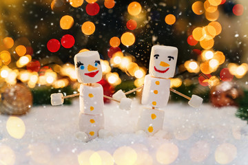 Marshmallow snowmen holding hands. Holiday concept.