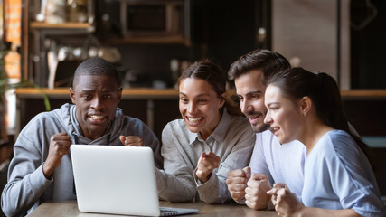 Excited diverse friends cheering watching match on laptop online