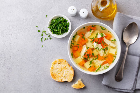 Chicken soup with vegetables in white bowl. Grey stone background. Copy space. Top view.