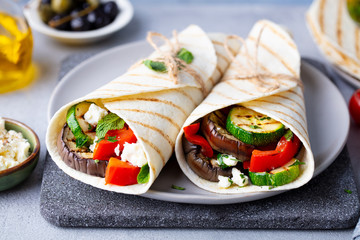 Keuken foto achterwand Snack Wrap sandwich with grilled vegetables and feta cheese on a plate. Grey background. Close up.