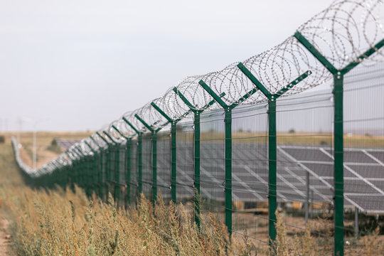 Solar power station protected from road by barbed wire fence. Fencing of sensitive sites with barbed wire.